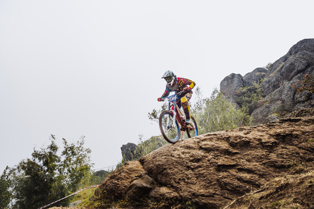 edge of cliff: Magnitogorsk, Russia - July 23, 2016: male young driver athlete on bike at edge of cliff during National championship downhill Editorial