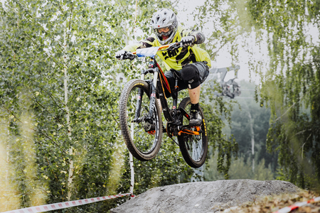magnitogorsk: Magnitogorsk, Russia - July 23, 2016: young rider athlete on bicycle jump over obstacles during National championship downhill