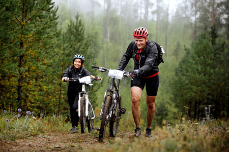 uphill: Revda, Russia - July 31, 2016: young couple of cyclists go uphill with your mountainbike during Regional competitions on cross-country bike Editorial