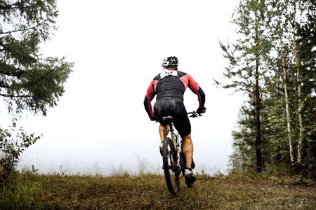 pieds sales: athlète cycliste monte à travers la forêt, vue de dos, les pieds sales Banque d'images