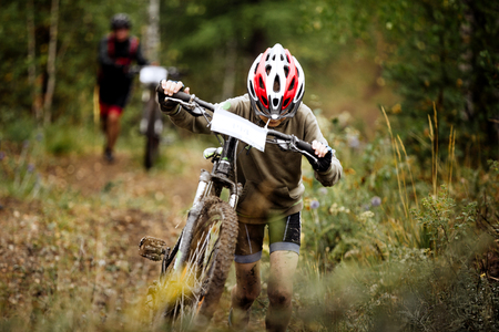 crosscountry: teen boy athlete mountainbike uphill on foot with his bicycle