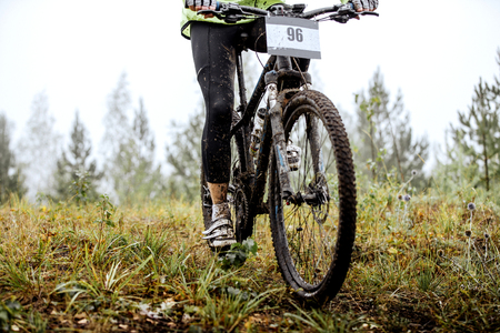 dirty feet: dirty feet of mountainbiker and bicycle wheel during competitions in cross-country