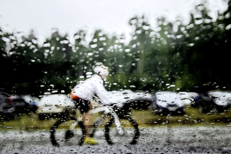 crosscountry: blurry image behind glass in rain athlete mountainbiker riding on street