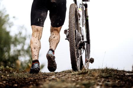 pieds sales: gros plan pieds sales athlète mountainbiker et la roue d'une bicyclette de sport