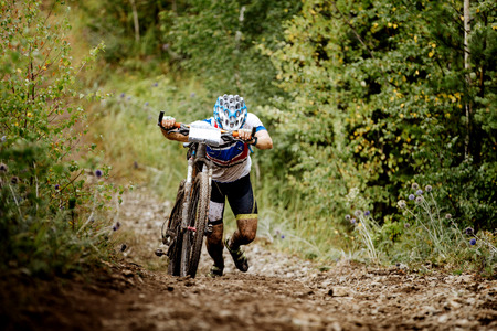 mountainbike: male athlete a cyclist walking uphill together with sport mountainbike