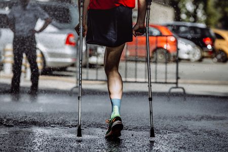 male athlete with a disability without a leg on crutches running marathon