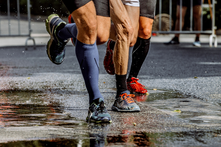 legs of three male marathon runners water splashes from under running shoes