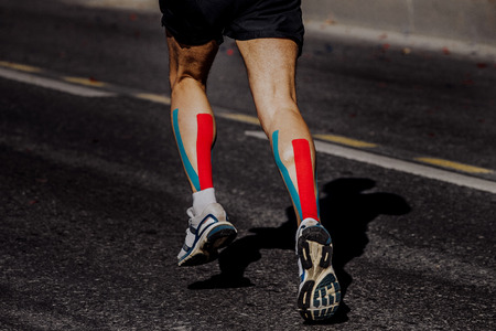 kinesio taping on muscles of calf male athlete running marathon