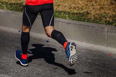 hombres corriendo: calcetines de compresión en los pies de un atleta de hombre que corre un maratón Foto de archivo