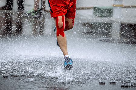 male athlete with tape on his knees running through a puddle of water, splashes and drops around feet Foto de archivo