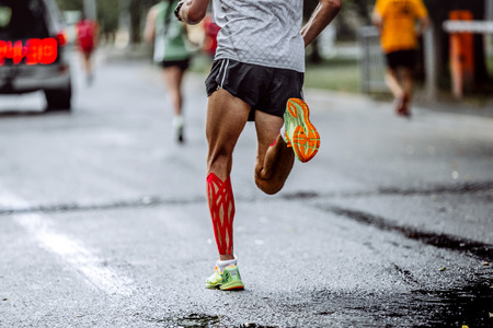 feet male athlete taping on calf muscles, running city marathon Foto de archivo