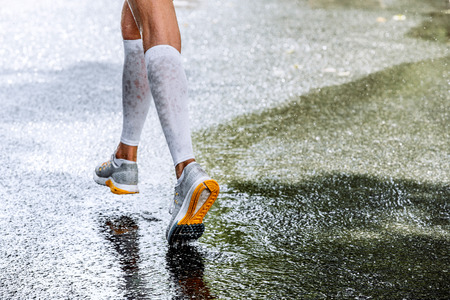 slender legs of women marathoner in compression socks, running through a puddle, water sprays Banque d'images