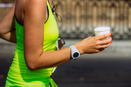 rival rivals rivalry season: closeup girls runner hand holding a glass of water after waterpoint Stock Photo