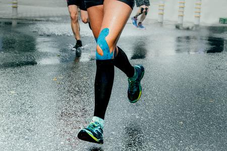 corredores pies chica en calcetines de compresión y grabación de rodillas, que se ejecuta en el asfalto mojado