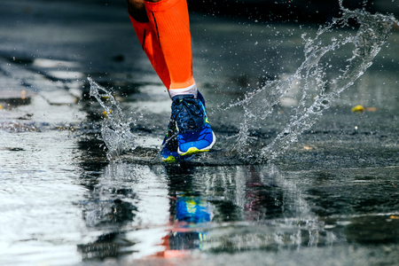 rivals rival rivalry season: legs men in marathon compression socks, running through a puddle, water sprays