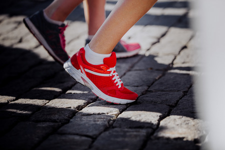rival rivals rivalry season: closeup of red sports shoes running on athlete foot Stock Photo
