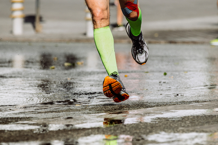 taping: feet men runners compression socks and knee taping running on wet asphalt Stock Photo
