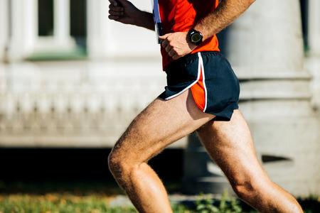 rivals rival rivalry season: athletic man runs a marathon on street, on hand watch