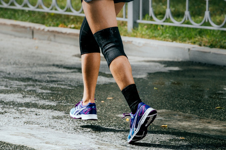legs women athletes in knee pad running sports race around city