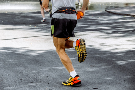 rival rivals rivalry season: male athlete running marathon in hand sponge with water Stock Photo