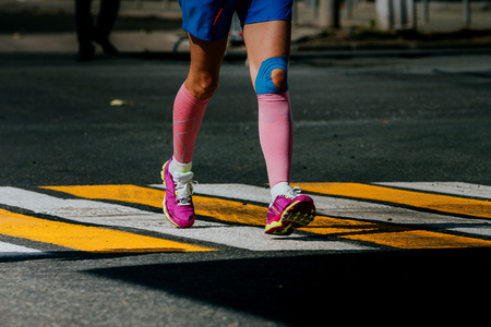 taping: legs women athletes in compression socks and taping knee running sports race Stock Photo