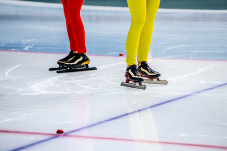 legs of two girls speed skaters at starting line during competition in speed skating Stock Photo