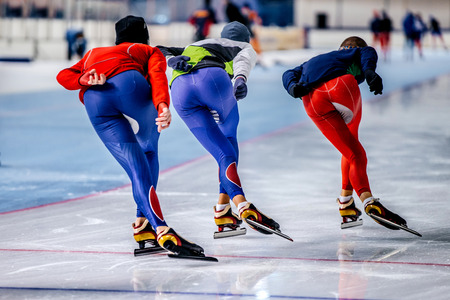 group of men skating on warm-up race before competitions in speed skating
