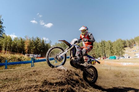 rear wheel: Kyshtym, Russia - July 17, 2016: racer on a motorcycle rides uphill on rear wheel during Ural Cup in Enduro