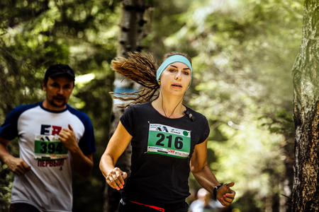 loose hair: Zlatoust, Russia - August 28, 2016: young active woman athlete runs in forest, loose hair during Mountain marathon Editorial