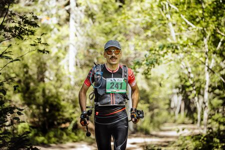 midlife: Zlatoust, Russia - August 28, 2016: male athlete midlife age runs in woods with nordic poles in hand during Mountain marathon