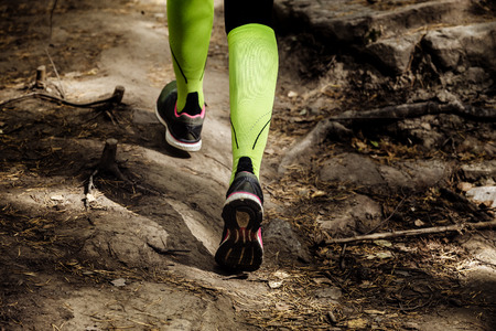 girl runs a marathon stone trail. closeup legs in compression socks and running shoes