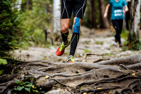 running marathon runner in forest. legs in compression socks, knee taping