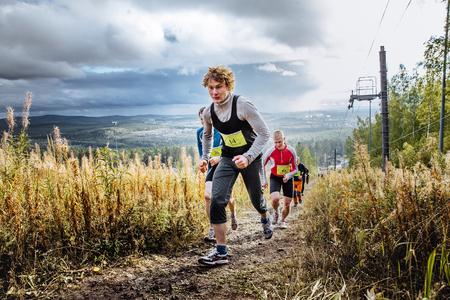 uphill: Revda, Russia - September 10, 2016: group of runners marathon runner ran uphill on blue sky background during marathon Vertical kilometer
