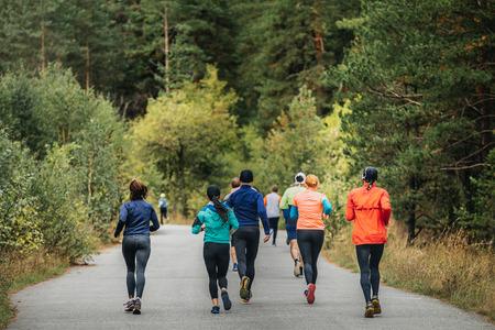 salud y deporte: volver corredores del grupo que se ejecuta en el otoño de parque durante una competición de maratón Foto de archivo