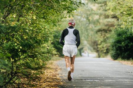 gerontology: back oldest male runner running in autumn Park during city marathon
