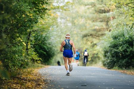 gerontology: back oldest male runner marathon running in autumn Park. yellow leaves on ground Stock Photo