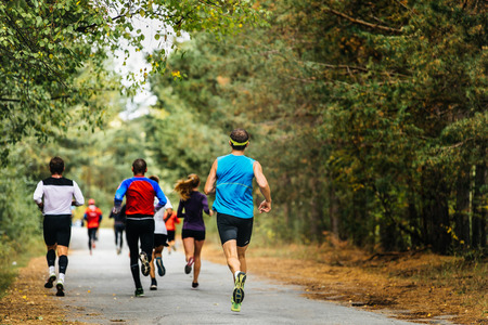 group young athletes running in autumn woods. yellow leaves on ground