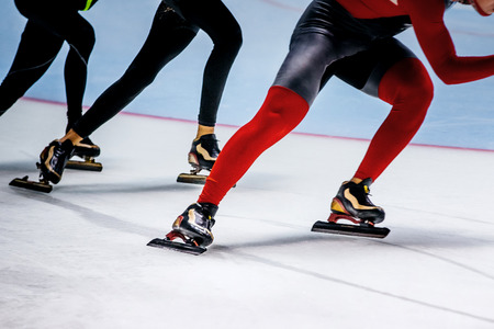one behind other men athletes skaters. professional competitions in speed skating