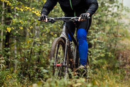 man mountain biking in autumn forest. active rest on nature