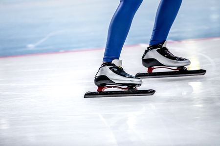 closeup slim feet women speed skaters in sports skates
