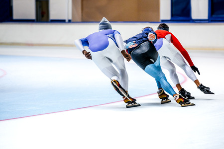 three athletes skating on ice sports arena. warm-up before competitions in speed skating Stock Photo