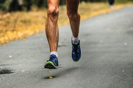 hairy male: hairy legs male runner running on asphalt road in autumn forest Stock Photo
