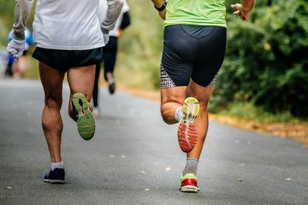 Nahaufnahme der Beine männliche Läufer laufen auf der Straße im Herbst Park mit gefallenen gelben Blättern Standard-Bild - 65584200