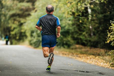 gerontology: active elderly man running down road in autumn Park