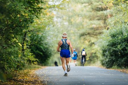 gerontology: sports elderly man athlete running in autumn forest marathon Stock Photo
