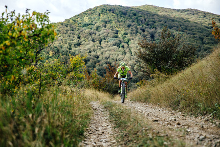 uphill: male rider cyclist riding uphill on a forest trail during Crimean race mountainbike Editorial