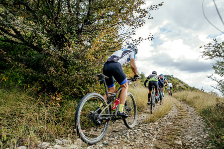 mountainbike: group of riders cyclists riding uphill one behind other during Crimean race mountainbike Editorial