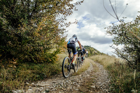uphill: group of cyclists on sports mountainbike riding uphill. Cycling competition