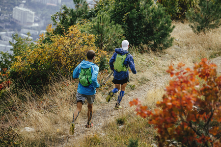 taping: two men running mountain trail with backpacks for running. compression socks and taping on feet Stock Photo