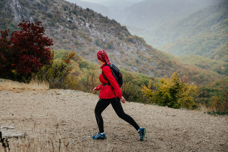 young girl hikers travelling walking a mountain trail in autumn rain weather